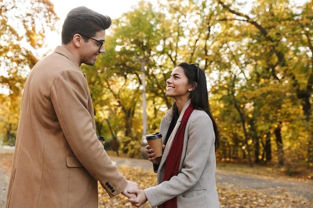 Portret van een jong stel dat afhaalkoffie drinkt uit papieren bekers en elkaar aankijkt tijdens het wandelen in het herfstpark