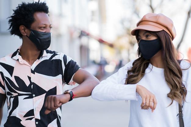 Portret van een jong stel dat een gezichtsmasker draagt en met hun ellebogen op elkaar tikt om hallo te zeggen terwijl ze buiten staan. nieuw normaal levensstijlconcept.