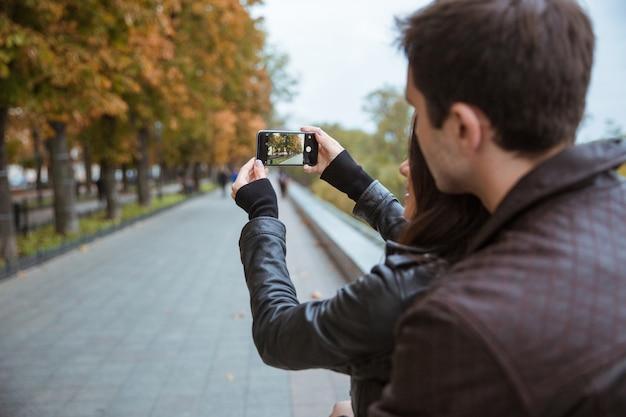 Portret van een jong stel dat foto op smartphone van herfstpark maakt