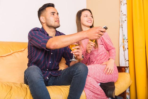 Portret van een jong stel dat lacht terwijl ze samen op een bank thuis zitten en tv kijken