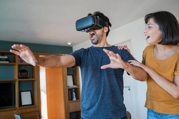Portret van een jong stel dat samen plezier heeft en videogames speelt met een vr-bril terwijl ze thuis blijven