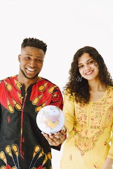 Portret van een jong stel, indiase vrouw en afrikaanse man met globe. geïsoleerd op een witte achtergrond.