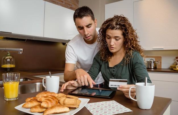 Portret van een jong stel met een elektronische tablet die de maandelijkse uitbetalingen van de creditcard bekijkt. elektronisch bankconcept.