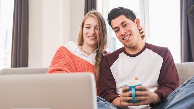 Portret van een jong stel tijdens een videogesprek met hun laptop terwijl ze thuis blijven Premium Foto