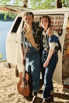 Portret van een jong stel wandelaars die naar de camera kijken terwijl ze hun vakantie hebben in de natuur aan het meer