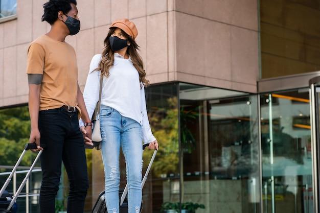 Portret van een jong toeristenpaar dat een beschermend masker draagt en een koffer draagt terwijl ze buiten op straat lopen. toeristisch concept