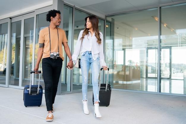 Portret van een jong toeristenpaar dat een koffer draagt terwijl ze buiten op straat lopen. toerisme concept.