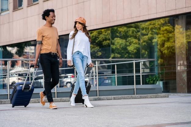 Portret van een jong toeristisch paar die koffer draagt tijdens het buiten lopen op straat