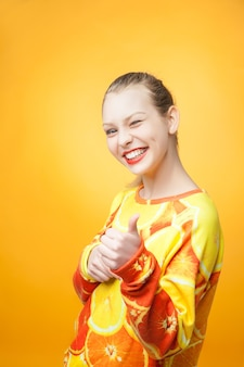 Portret van een jong, vrij grappig lachend meisje met een oranje bedrukt sweatshirt