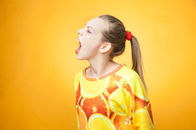 Portret van een jong, vrij grappig schreeuwend meisje met een oranje bedrukt sweatshirt
