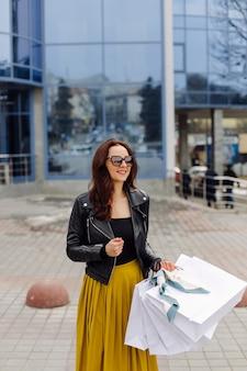 Portret van een jong vrij stijlvol meisje dat de boodschappentassen houdt en in een goed humeur uitkijkt. ideaal winkelen.