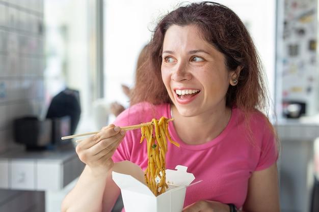 Portret van een jong vrolijk meisje chinese noedels eten in een café en kijkt uit het raam. het concept van een gezonde aziatische keuken.