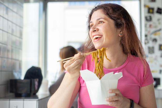 Portret van een jong vrolijk meisje dat chinese noedels eet in een koffie en uit het venster kijkt