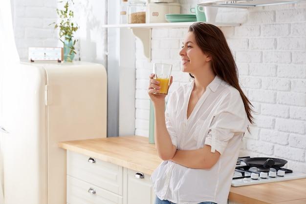 Portret van een jong vrouwen drinkwater in de keuken thuis