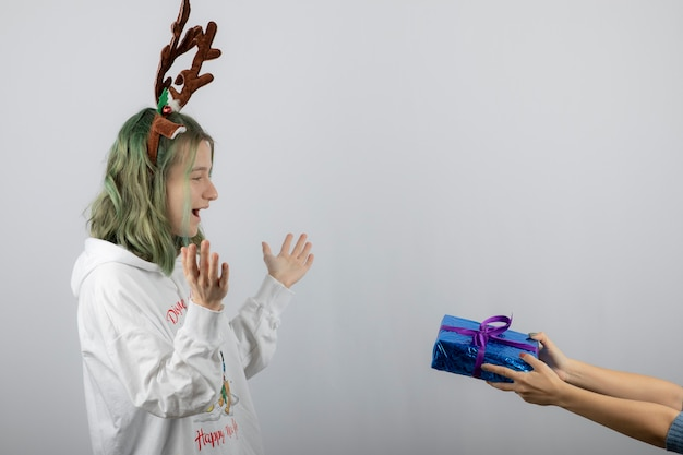Portret van een jong vrouwenmodel dat een cadeautje geeft.