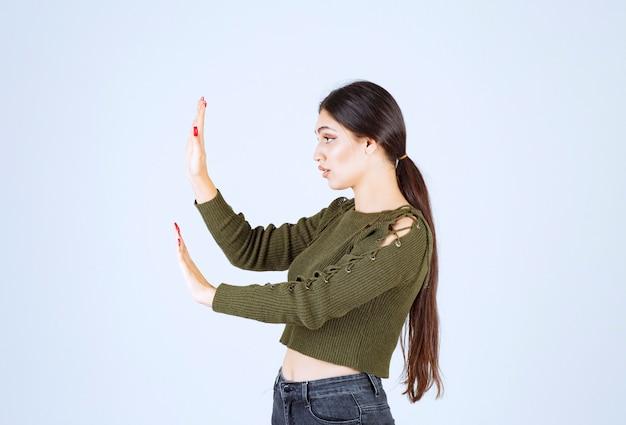Portret van een jong vrouwenmodel dat iets in de kant over witte muur duwt.