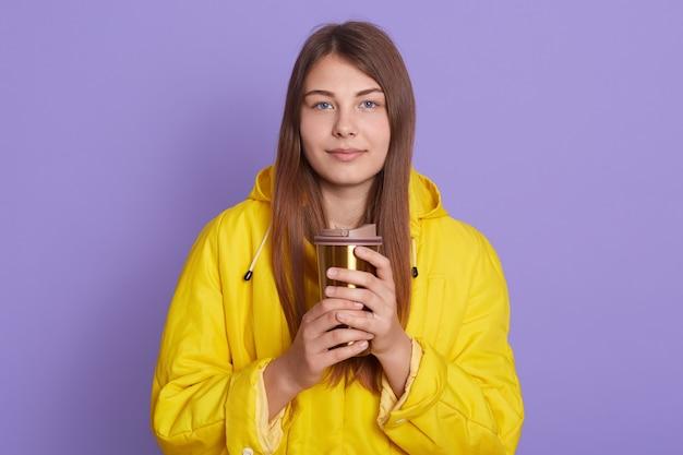 Portret van een jonge aantrekkelijke dame met lang steil haar in een gele jas, die thermomok koffie houdt om in de hand te gaan terwijl ze naar de camera kijkt op een lila achtergrond, heeft een rustige en ontspannen uitdrukking.