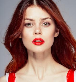 Portret van een jonge aantrekkelijke en mooie vrouw met rode lippen, rood vliegend haar
