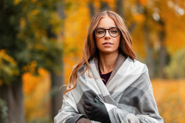 Portret van een jonge aantrekkelijke jonge vrouw hipster in stijlvolle bril in een jas in een vintage gebreide sjaal op een achtergrond van gouden gebladerte in het park. vrij mooi meisje geniet van een warme herfstdag