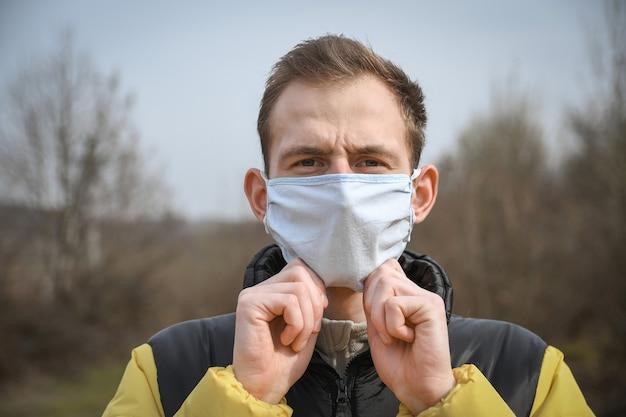 Portret van een jonge aantrekkelijke kerel in een medisch masker.