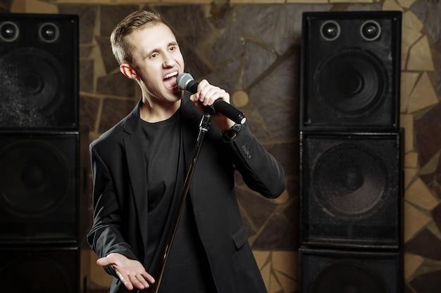 Portret van een jonge aantrekkelijke man die met een microfoon zingt