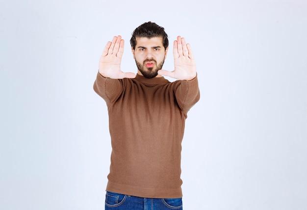Portret van een jonge aantrekkelijke man die met zijn handen stopt.