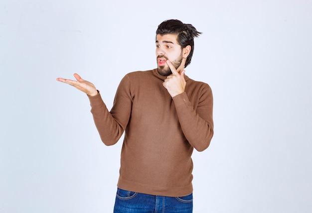 Portret van een jonge aantrekkelijke man model met baard hand tonen