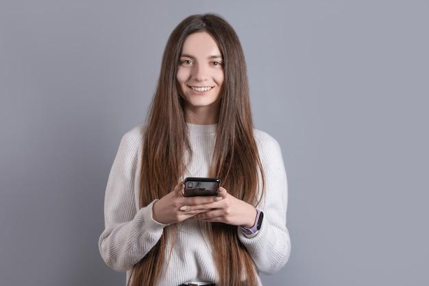 Portret van een jonge aantrekkelijke meisjesvrouw met donker lang haar die gemakkelijk glimlachen en de smartphone van de celtelefoon houden