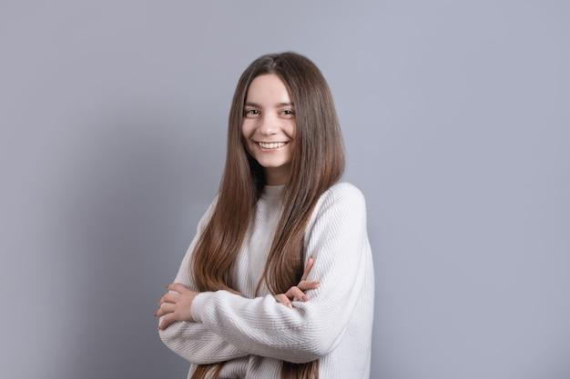 Portret van een jonge aantrekkelijke meisjesvrouw met donker lang haar die gemakkelijk glimlachen