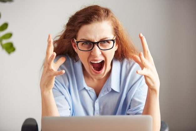 Portret van een jonge aantrekkelijke onderneemster met gefrustreerde blik die aan laptop werkt