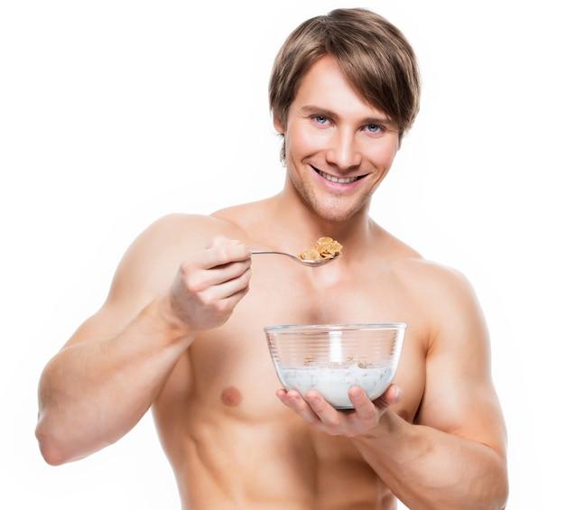 Portret van een jonge aantrekkelijke spiermens die vlokken met melk eet - die op witte muur wordt geïsoleerd.