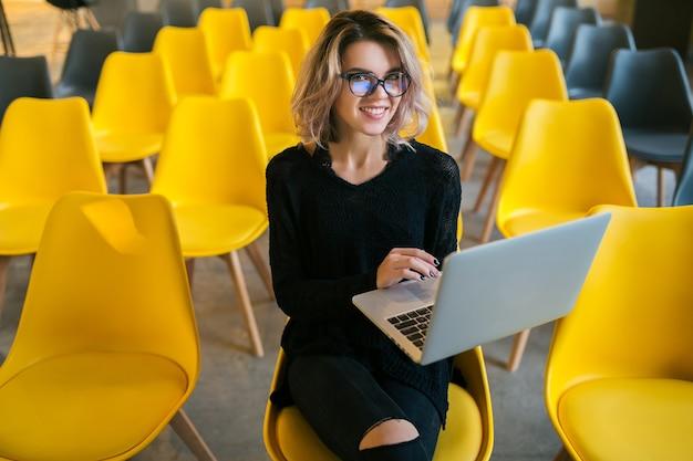 Portret van een jonge aantrekkelijke vrouw die in de collegezaal zit en aan een laptop werkt die een bril draagt