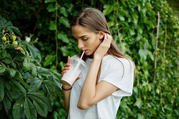 Portret van een jonge aantrekkelijke vrouw die in een wit t-shirt een milkshake drinkt