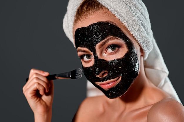 Portret van een jonge aantrekkelijke vrouw met een handdoek op haar hoofd die een zwart reinigend masker met een borstel toepast op haar gezicht op een grijze muur.