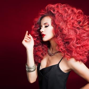 Portret van een jonge aantrekkelijke vrouw met een zeer weelderige kapsel. rood haar