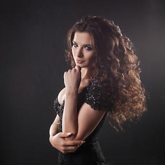 Portret van een jonge aantrekkelijke vrouw met prachtig krullend haar. aantrekkelijke brunette.