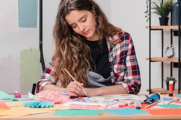 Portret van een jonge aantrekkelijke vrouwelijke kunstenaar die op papier schildert