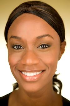 Portret van een jonge african american vrouw die lacht op de camera