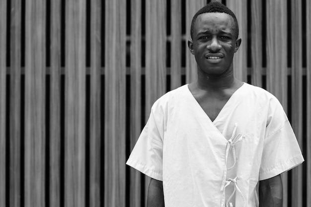 Portret van een jonge afrikaanse man als ziekenhuispatiënt buiten in zwart-wit