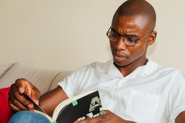Portret van een jonge afrikaanse man met bril lezen van het boek