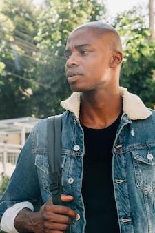 Portret van een jonge afrikaanse man met een rugzak op zijn schouder wegkijken