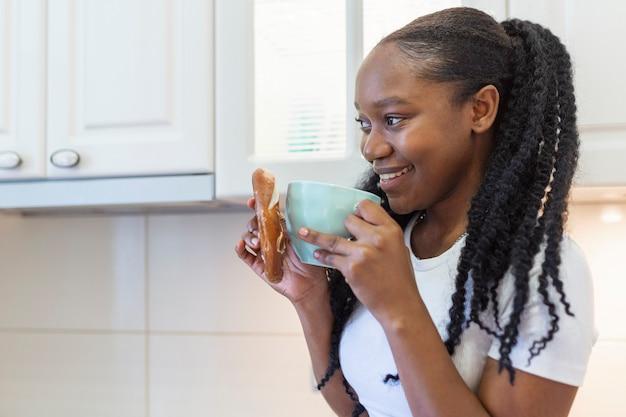 Portret van een jonge afrikaanse vrouw die een kopje koffie drinkt pearl from the east. glimlachende vrouw met koffiemok.