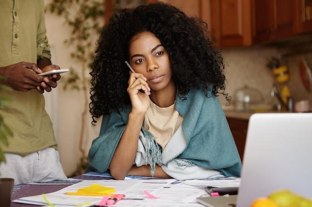 Portret van een jonge afrikaanse vrouw met afro kapsel beantwoorden oproep van bank