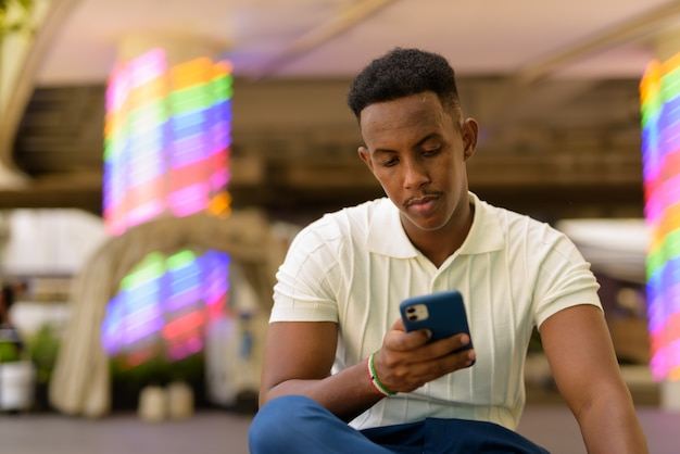 Portret van een jonge afrikaanse zakenman die vrijetijdskleding draagt en een mobiele telefoon gebruikt terwijl hij zit