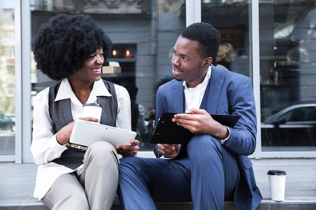 Portret van een jonge afrikaanse zakenman en een onderneemster die een bureauonderbreking nemen