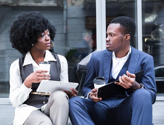 Portret van een jonge afrikaanse zakenman en onderneemsterzitting samen buiten het bureau