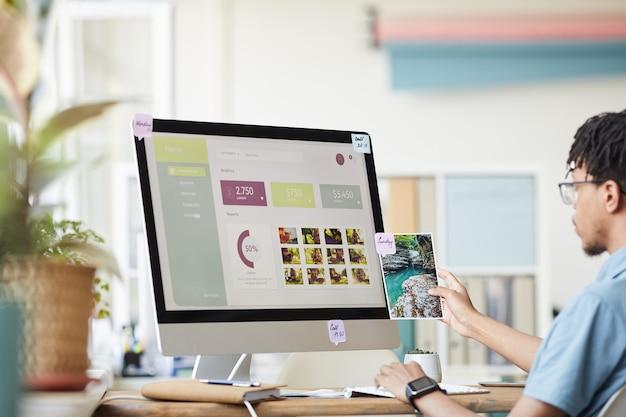 Portret van een jonge afro-amerikaanse fotograaf beheren foto beurs tijdens het gebruik van computer aan balie in kantoor aan huis met foto website op scherm, kopie ruimte
