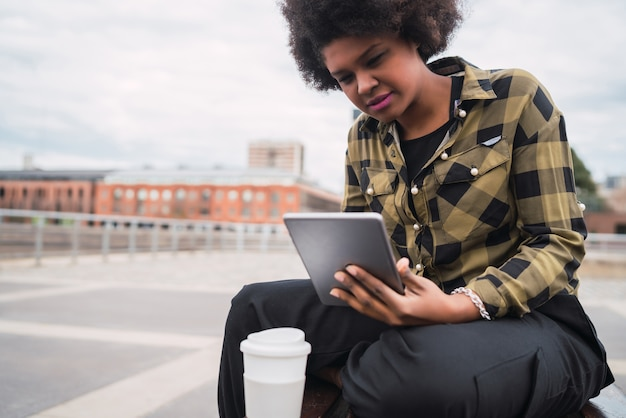 Portret van een jonge afro-amerikaanse latijns-vrouw met behulp van haar digitale tablet zittend op een bankje buitenshuis. technologie concept.