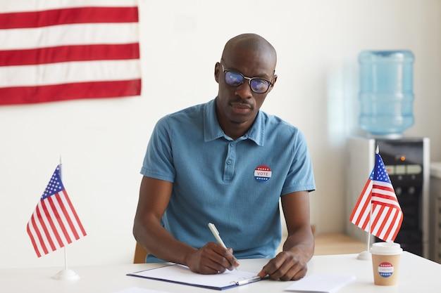 Portret van een jonge afro-amerikaanse man aan het werk bij het stembureau op de dag van de verkiezingen en kiezers registreren, kopie ruimte