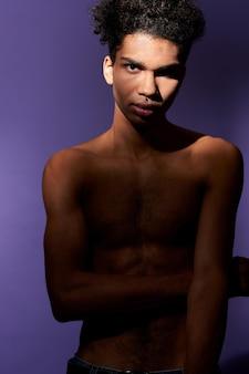 Portret van een jonge afro-amerikaanse man die in een casual pose staat en op zoek is naar een transgender-cameramodel